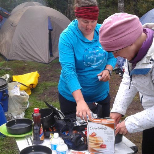 Participants and City of St. John's staff cooking pancakes on dragonfly stoves.