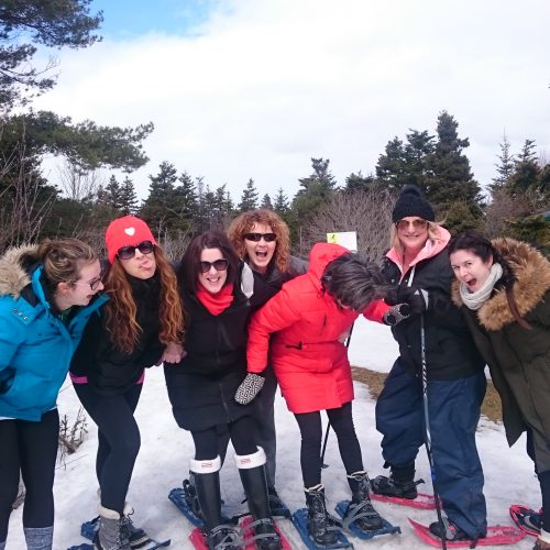 Group of participants having fun on snowshoe trail.
